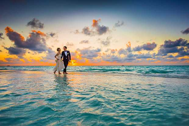 Wedding photoshoot of bridegroom and bride at sunset by the sea